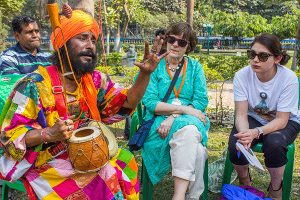 A man in colorful traditional Indian dress speaks while holding an instrument as two women look on.