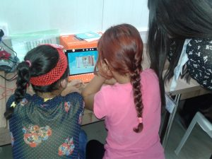 Two young girls work at a small orange computer as an adult woman looks on.