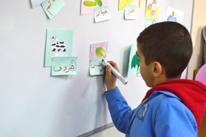 A young boy stands at a white board and writes in Arabic.
