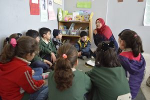 A teacher sits in a group of students reading.