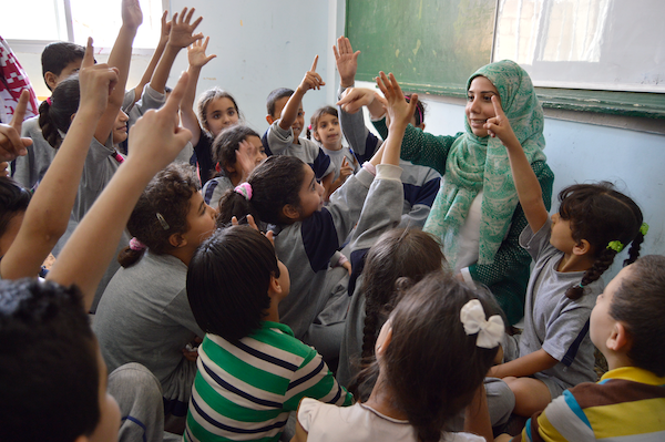 A woman stands in front of her class surrounded by young students.