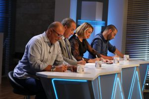 Contestants bend over a desk on set at Andi Hulm. They are very focused as they write notes on the paper in front of them.