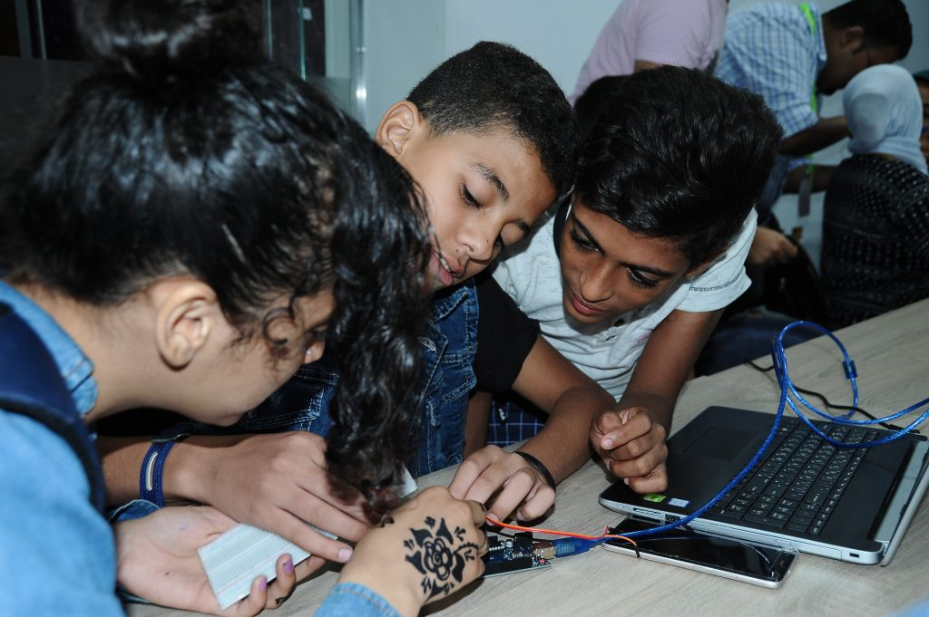 Four students work on a circuit board.
