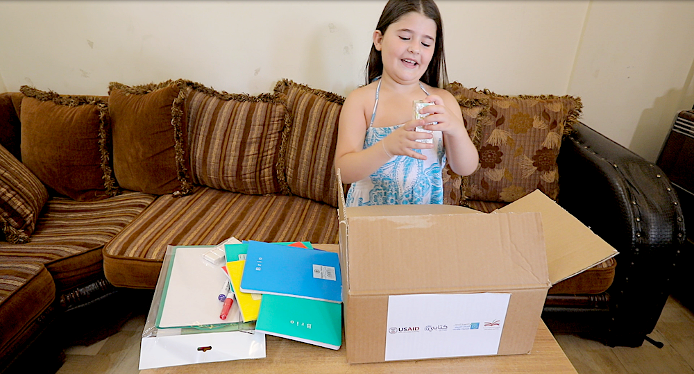 A young girl opens a box of educational supplies.