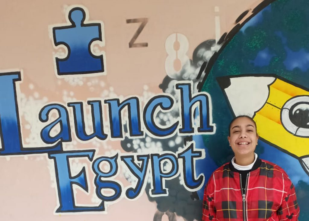 A student smiles in front of a sign that reads 'Launch Egypt' in blue on the Launch Egypt campus in Cairo, Egypt