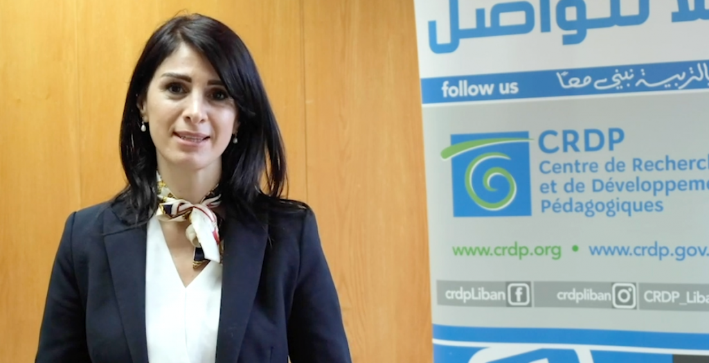A woman in a dark blue blazer with a white shirt and scarf around her neck stands facing the camera. A banner in Arabic and French is behind her to the right.