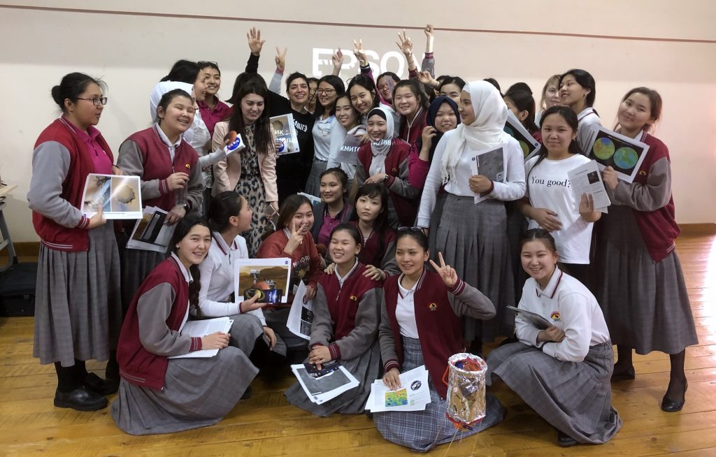 A group of girls in uniform and one adult pose while holding up photos and certificates.