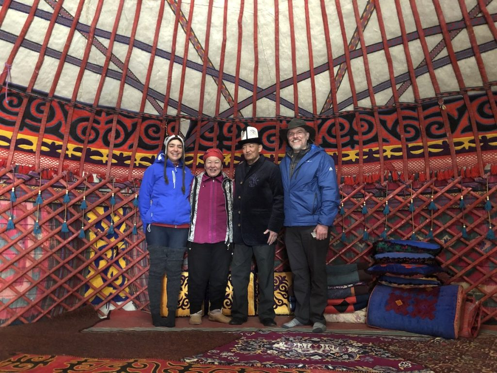 Four adults stand inside a large traditional dwelling in Kyrgyzstan.