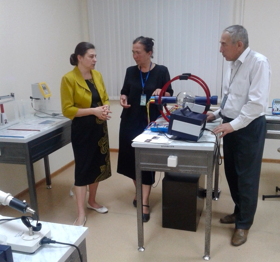 Two women and a man talk while standing next to lab equipment.