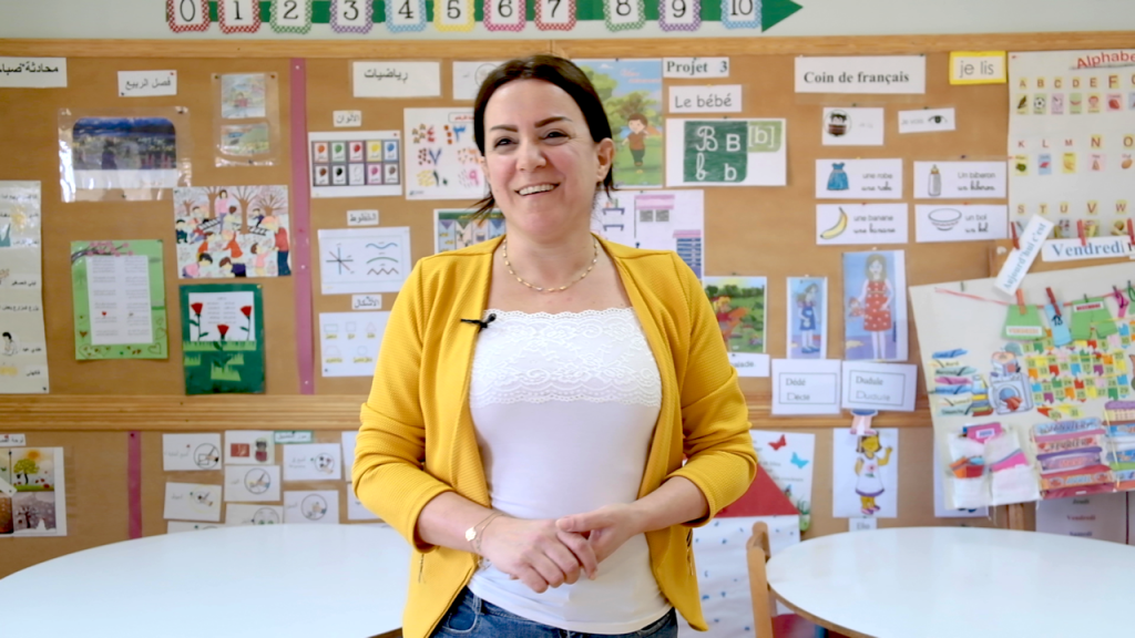 A woman in a white shirt and yellow cardigan stands looking at the camera in a classroom.