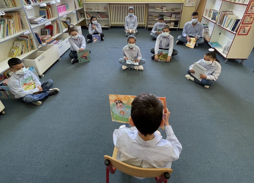 A boy sits in front of his class reading a book to a group of children wearing masks.